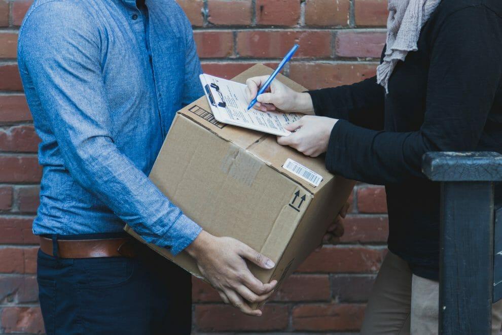 man signing for shipping box 4460x4460
