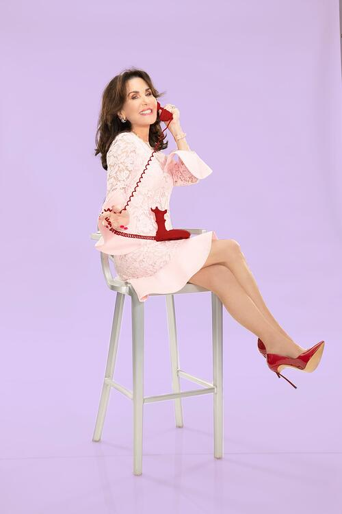 Robin McGraw sitting on a stool answering the phone