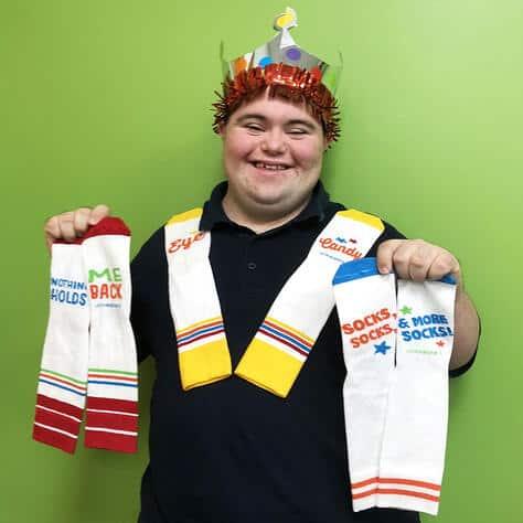 John Cronin (John's Crazy Socks) wearing crown and holding socks